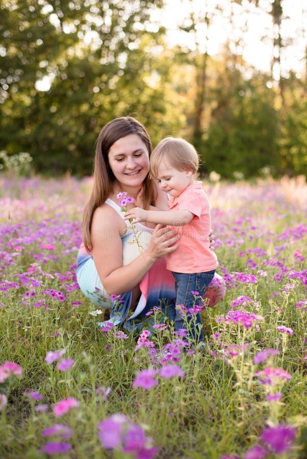 Retrato da jovem mulher que abraça seu filho pequeno da criança em um prado ensolarado fotografia de stock