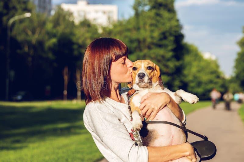Retrato da jovem mulher que beija seu cão bonito do lebreiro Amor, feliz, beijando o cachorrinho fotos de stock