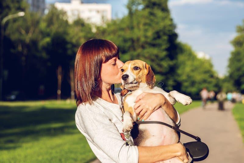 Retrato da jovem mulher que beija seu cão bonito do lebreiro Amor, feliz, beijando o cachorrinho fotos de stock royalty free