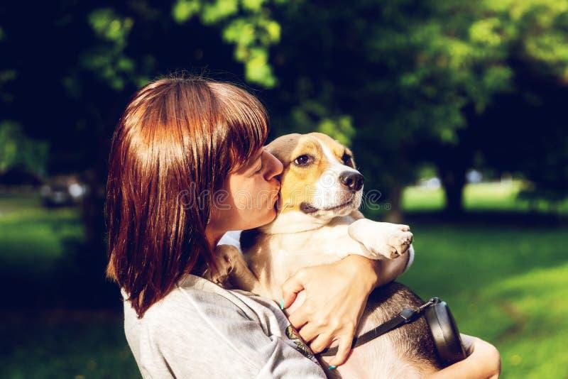 Retrato da jovem mulher que beija seu cão bonito do lebreiro Amor, feliz, beijando o cachorrinho foto de stock