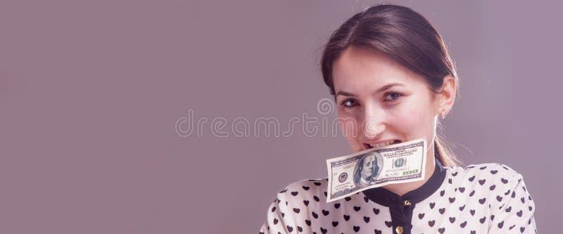 Retrato da jovem mulher que come o dinheiro do dólar americano como o símbolo da corrupção na política, negócio, diplomacia foto de stock royalty free