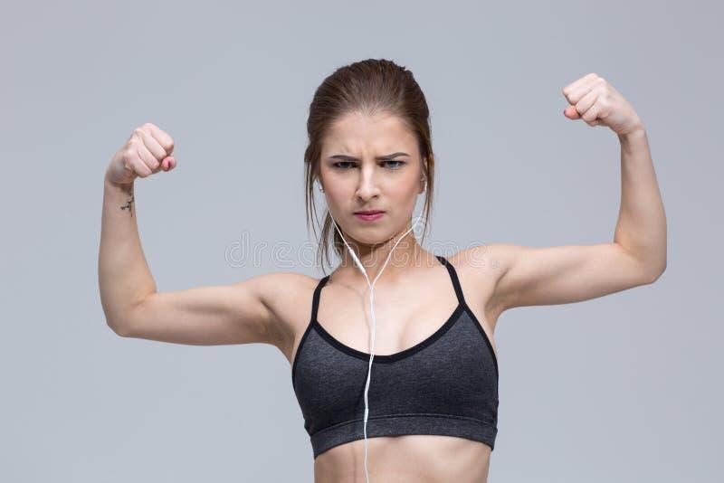 Retrato da jovem mulher que dobra seu bíceps imagens de stock