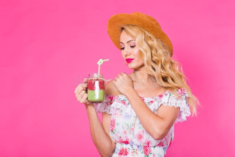Retrato da jovem mulher que guarda e que bebe o milk shake verde saboroso do batido no fundo cor-de-rosa imagem de stock royalty free