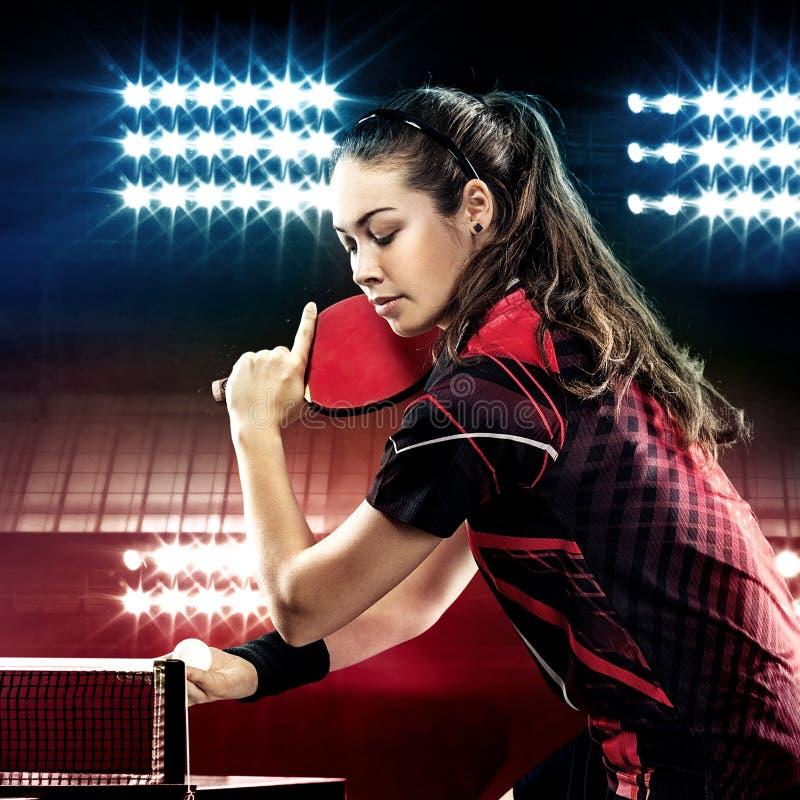 Retrato da jovem mulher que joga o tênis no preto foto de stock