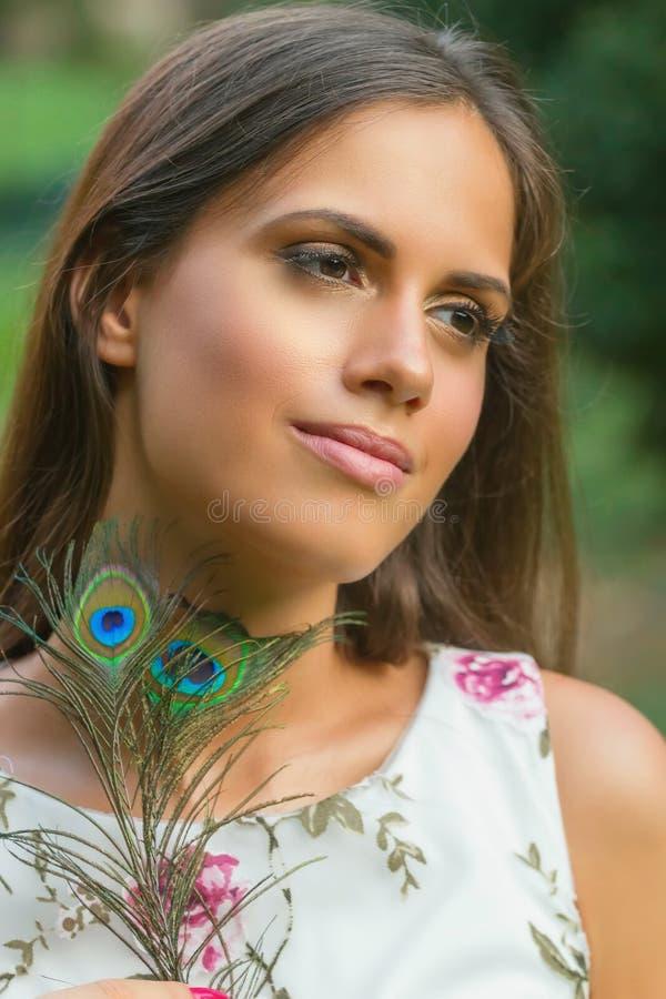Retrato da jovem mulher que mantém a pena do pavão exterior fotos de stock