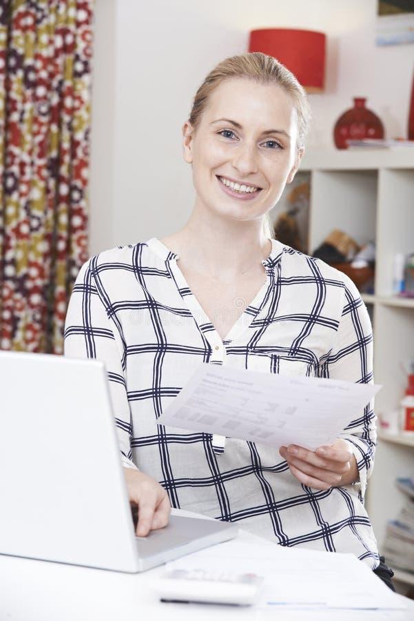 Retrato da jovem mulher que olha contas domésticas imagens de stock royalty free