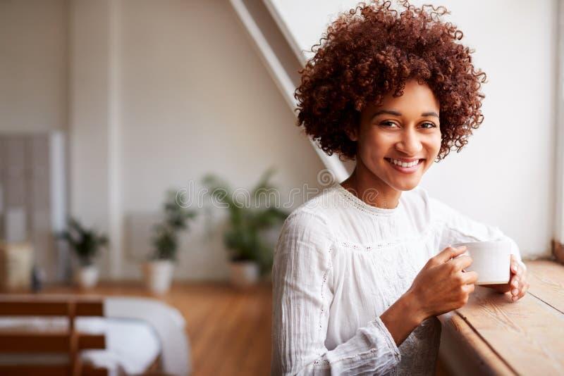 Retrato da jovem mulher que relaxa no apartamento do sótão que olha fora da janela com bebida quente imagem de stock royalty free