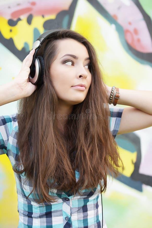 Retrato da jovem mulher que senta-se na parede dos grafittis foto de stock royalty free