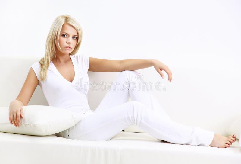 Retrato da jovem mulher que senta-se no sofá em casa imagens de stock