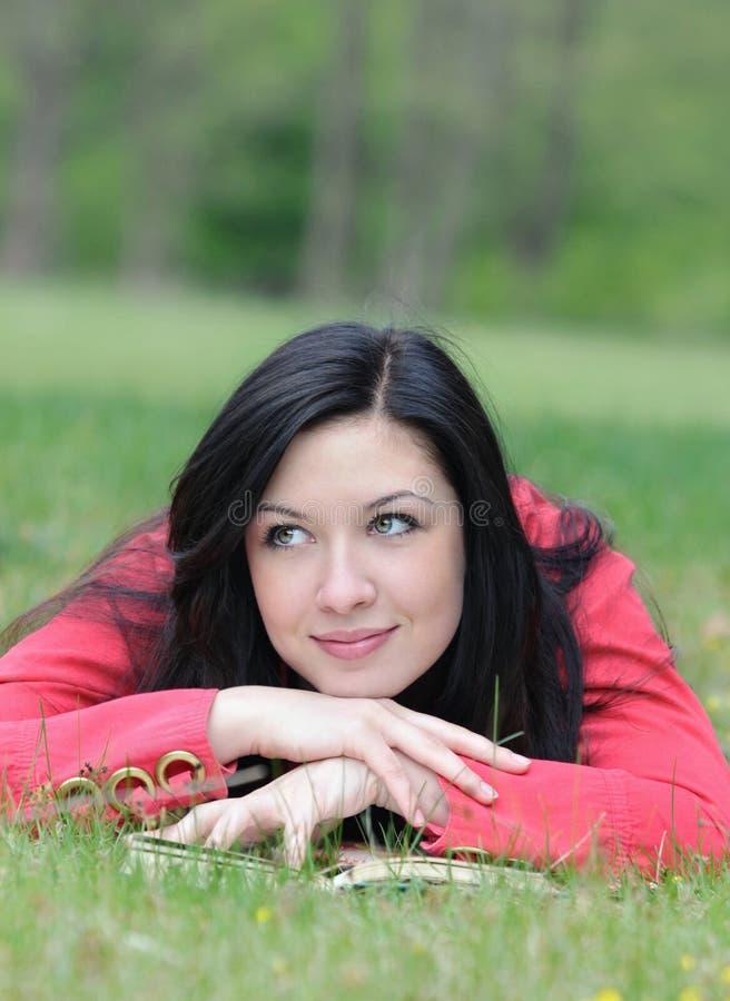 Retrato da jovem mulher que tem um resto com o livro na grama no imagem de stock