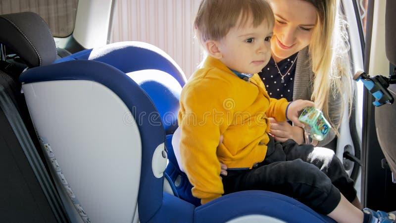 Retrato da jovem mulher que toma seu filho fora do banco de carro da segurança das crianças imagem de stock