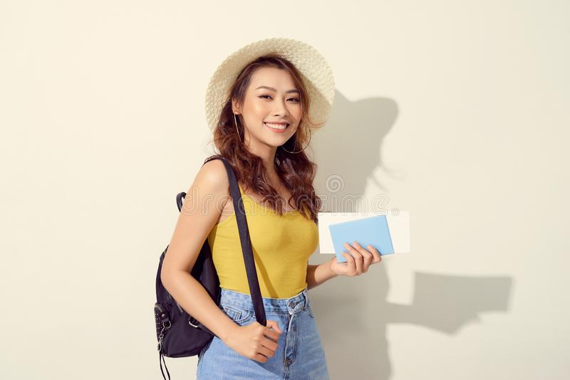 Retrato da jovem mulher que veste o equipamento na moda, chapéu de palha, curso com trouxa e guardando o bilhete do voo, passapor imagem de stock