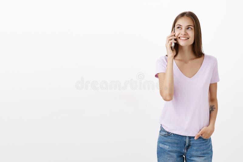 Retrato da jovem mulher segura feliz e despreocupada socisble com tatuagem em olhar deleitado de sorriso do t-shirt branco acima imagem de stock royalty free