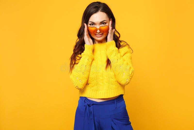 Retrato da jovem mulher segura na camiseta, calças azul que guarda os vidros do coração, olhando a câmera isolada no amarelo fotos de stock