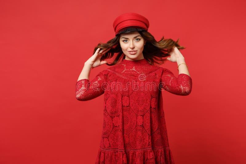Retrato da jovem mulher segura no vestido e no tampão do laço que guardam o cabelo que olha a câmera na parede vermelha brilhante foto de stock