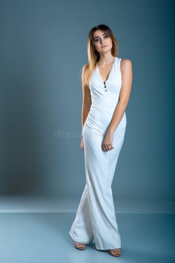 Retrato da jovem mulher 'sexy' bonita com macacão elegante, no fundo do cinza azul Morena nova atrativa com posição longa do cabe imagem de stock royalty free