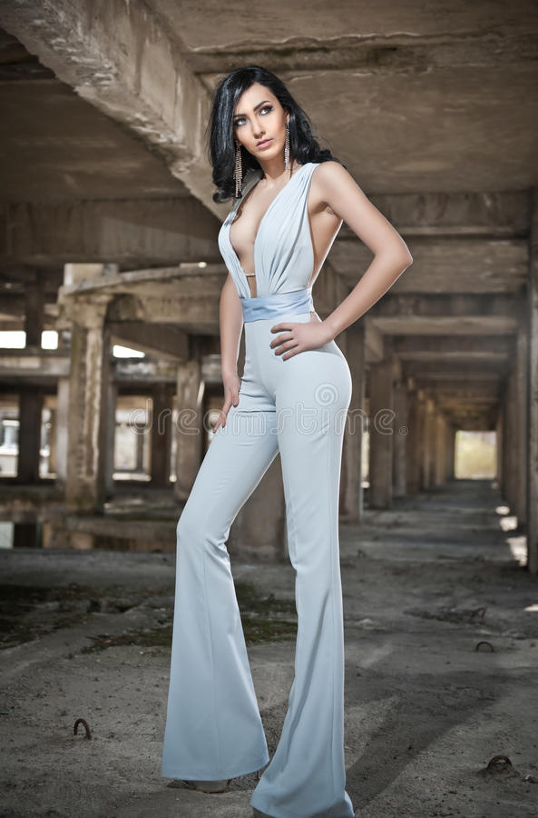Retrato da jovem mulher 'sexy' bonita com macacão elegante, no fundo urbano Morena nova atrativa com cabelo longo foto de stock royalty free