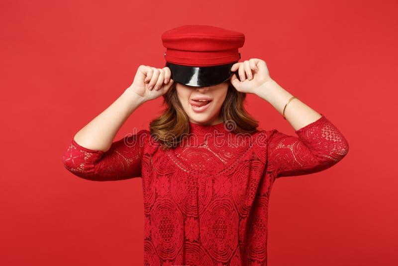 Retrato da jovem mulher 'sexy' no vestido do laço que cobre os olhos com o tampão, mostrando a língua isolada no fundo vermelho b imagens de stock