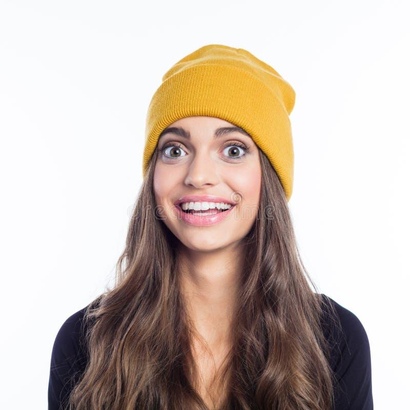 Retrato da jovem mulher surpreendida que veste o chapéu amarelo do beanie fotos de stock