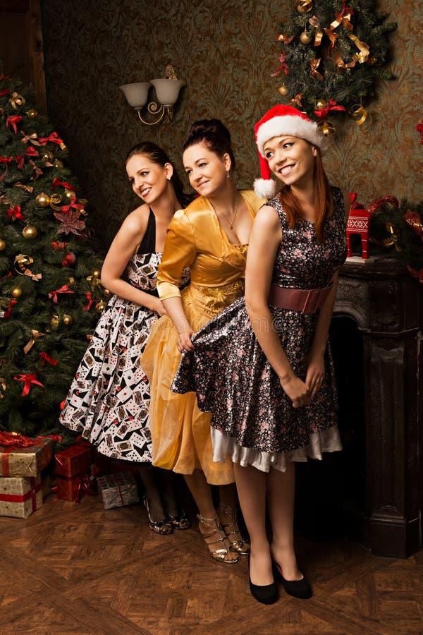 Retrato da jovem mulher três que levanta perto do Natal decorado t fotografia de stock