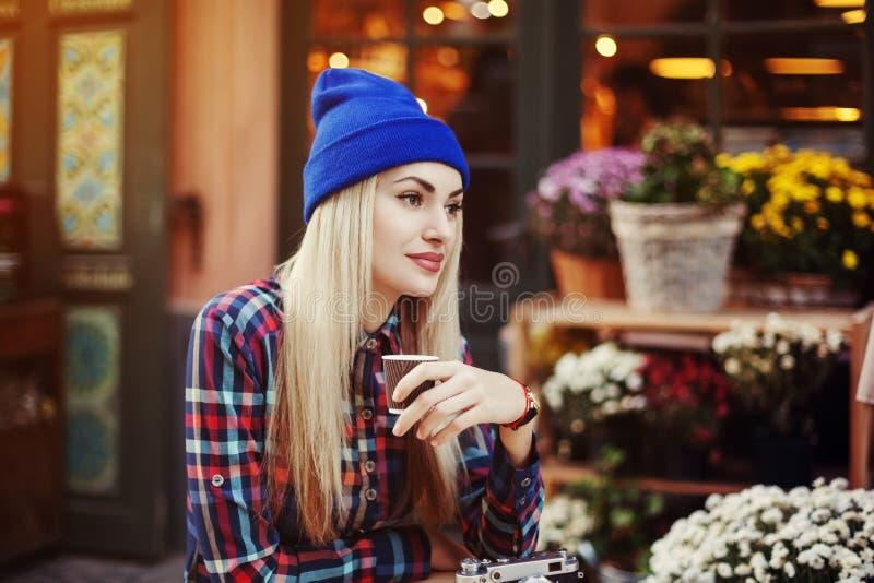 Retrato da jovem senhora à moda bonita que senta-se no café da rua e no café bebendo Moderno com a câmera retro velha foto de stock royalty free