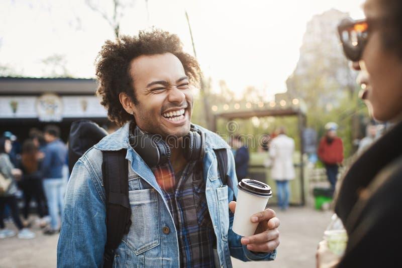 retrato da Lado-vista do indivíduo afro-americano bonito elegante com penteado afro que ri para fora ruidosamente sobre o gracejo fotos de stock