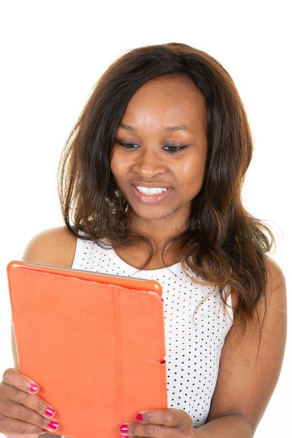 Retrato da leitura alegre da mulher afro-americano bonita algo na tabuleta eletrônica no fundo branco do estúdio imagens de stock