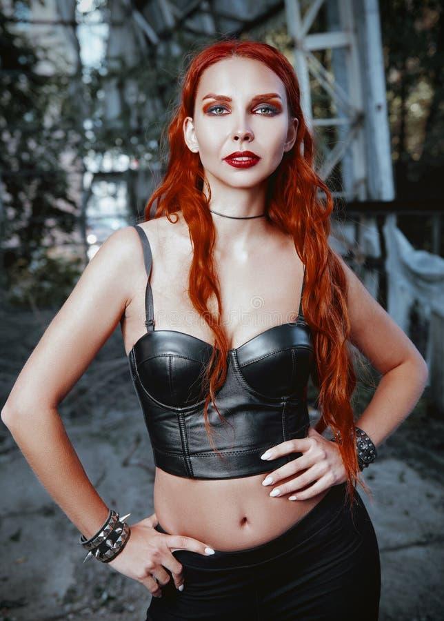Retrato da linda garota de rock de cabelo vermelho modelo informal em lugar abandonado Menina sedutora vestida de calça preta fotos de stock royalty free
