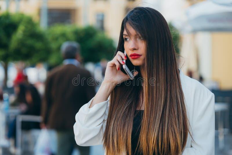 Retrato da linda jovem usando seu celular na rua fotografia de stock royalty free