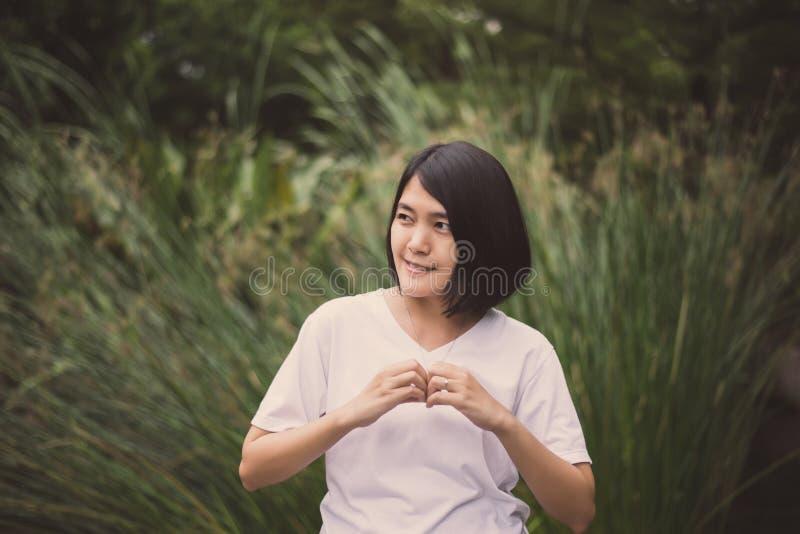 Retrato da linda mulher asiática cabelo curto mostrando mãos forma de coração, feliz e sorridente, pensamento positivo foto de stock royalty free