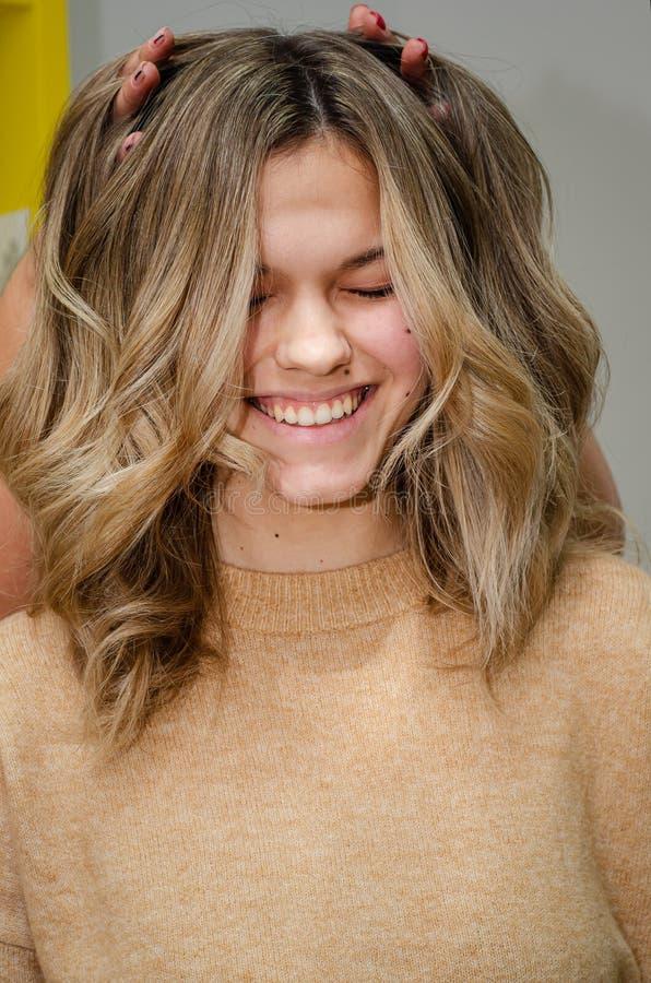 Retrato da linda mulher caucasiana após colorir o cabelo Hairstylist coloca dedos em modelos de cabelo e a faz rir fotos de stock royalty free