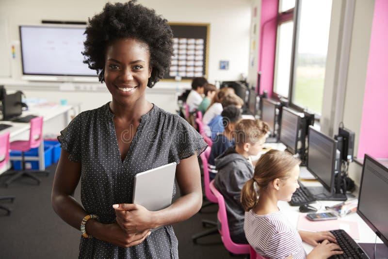 Retrato da linha de ensino de Holding Digital Tablet do professor fêmea de estudantes da High School que sentam-se por telas na c foto de stock