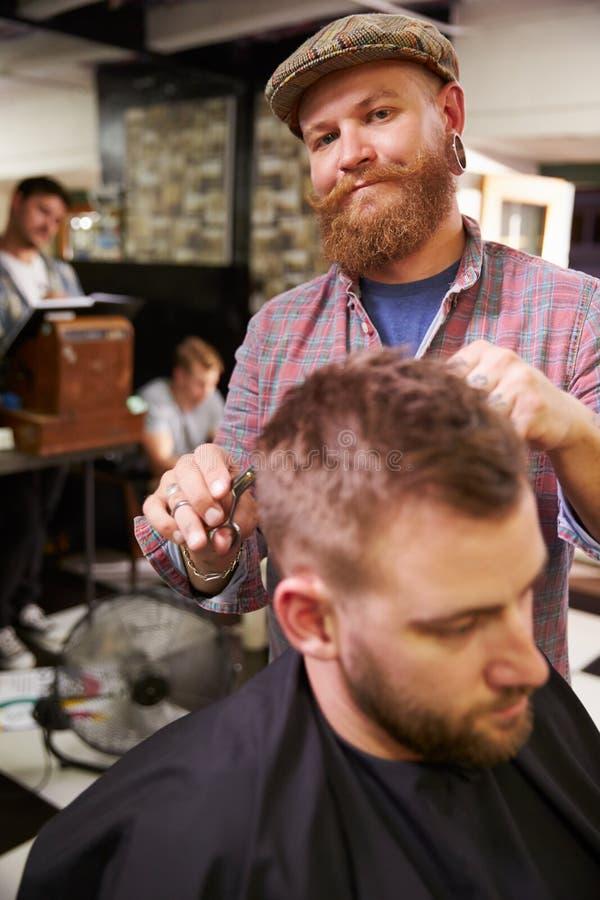 Retrato da loja masculina de Barber Giving Client Haircut In imagem de stock royalty free