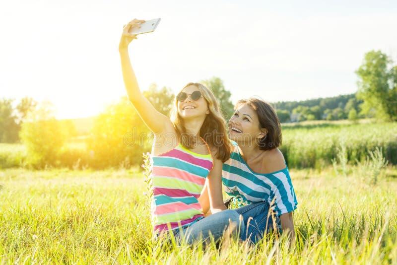 Retrato da mãe adulta bonita e seu do adolescente da filha que fazem um selfie usando o telefone esperto e o sorriso fotografia de stock royalty free