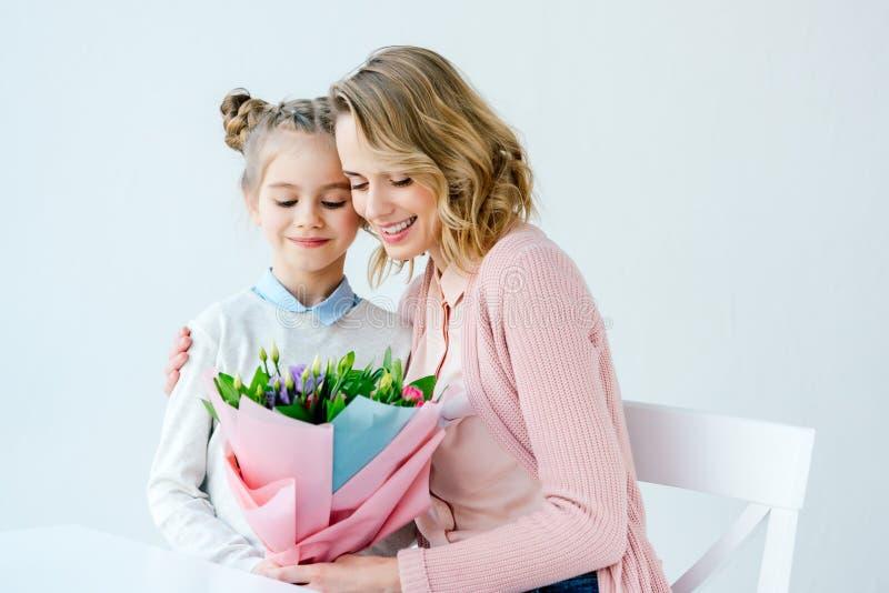 retrato da mãe de sorriso que abraça a filha pequena com o ramalhete bonito das flores, mães felizes foto de stock