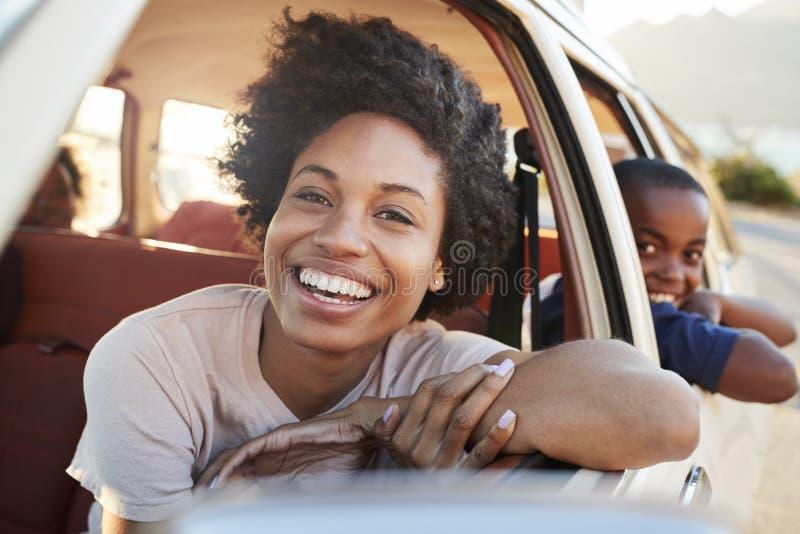 Retrato da mãe e das crianças que relaxam no carro durante a viagem por estrada fotografia de stock royalty free