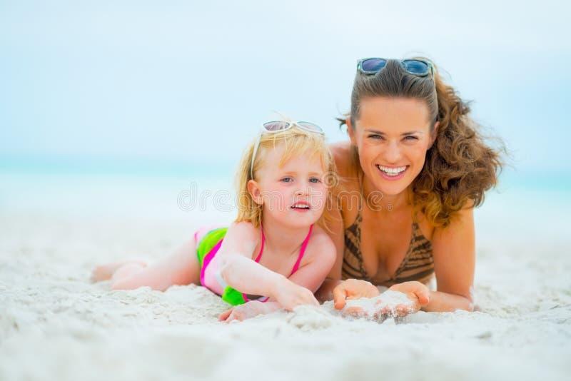 Retrato da mãe e do bebê de sorriso na praia fotografia de stock royalty free