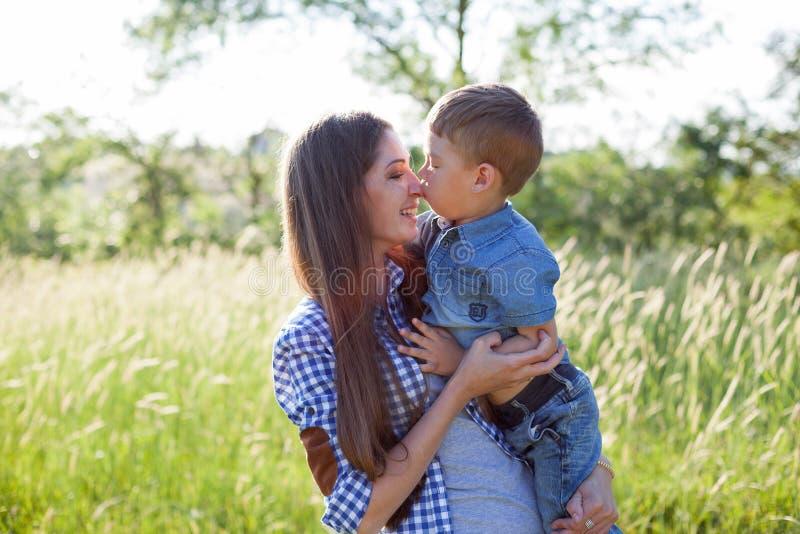 Retrato da mãe e do filho contra a família verde das árvores imagem de stock