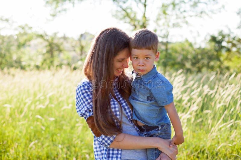 Retrato da mãe e do filho contra a família verde das árvores imagem de stock royalty free