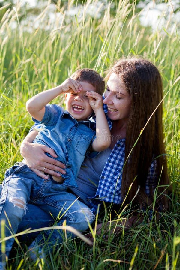 Retrato da mãe e do filho contra a família verde das árvores fotografia de stock royalty free