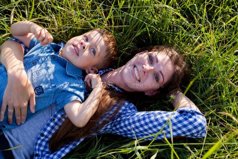 Retrato da mãe e do filho contra a família verde das árvores fotos de stock