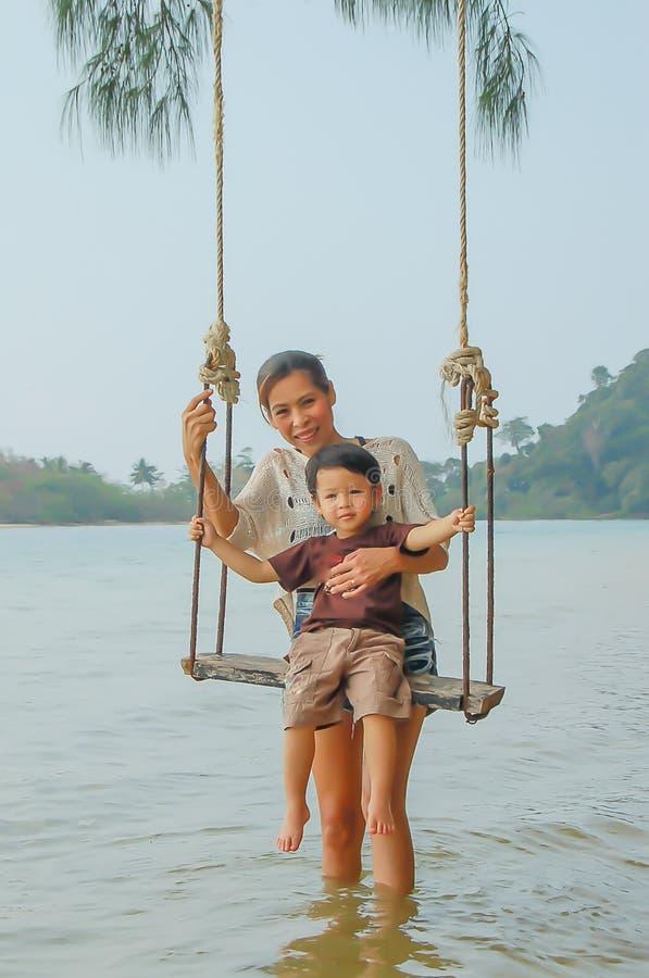Retrato da mãe e do filho que jogam a cadeira do balanço no mar fotografia de stock royalty free