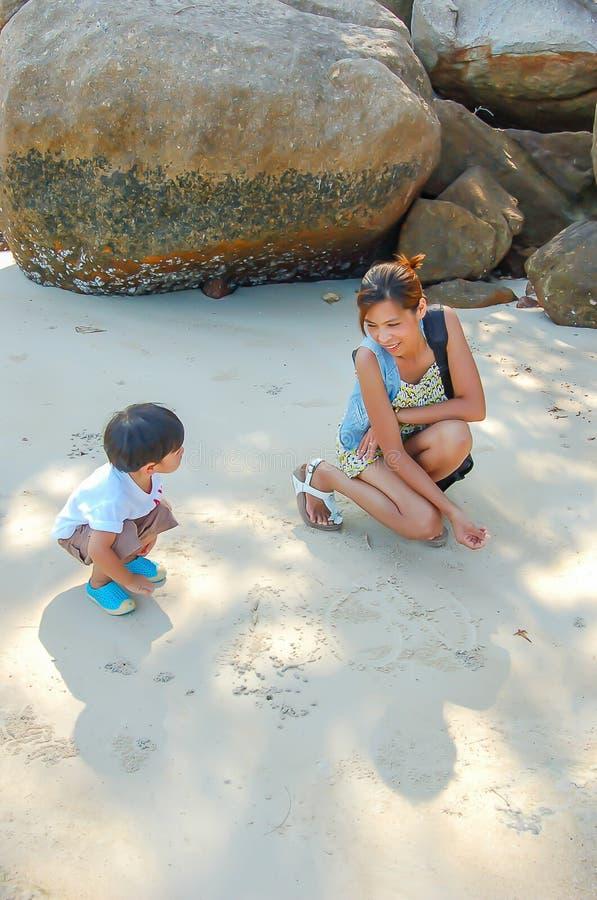 Retrato da mãe e do filho que jogam com a areia pelo mar fotos de stock royalty free