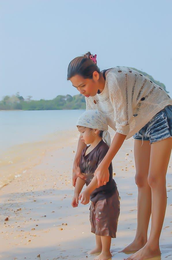 Retrato da mãe e do filho que jogam com a areia pelo mar foto de stock royalty free