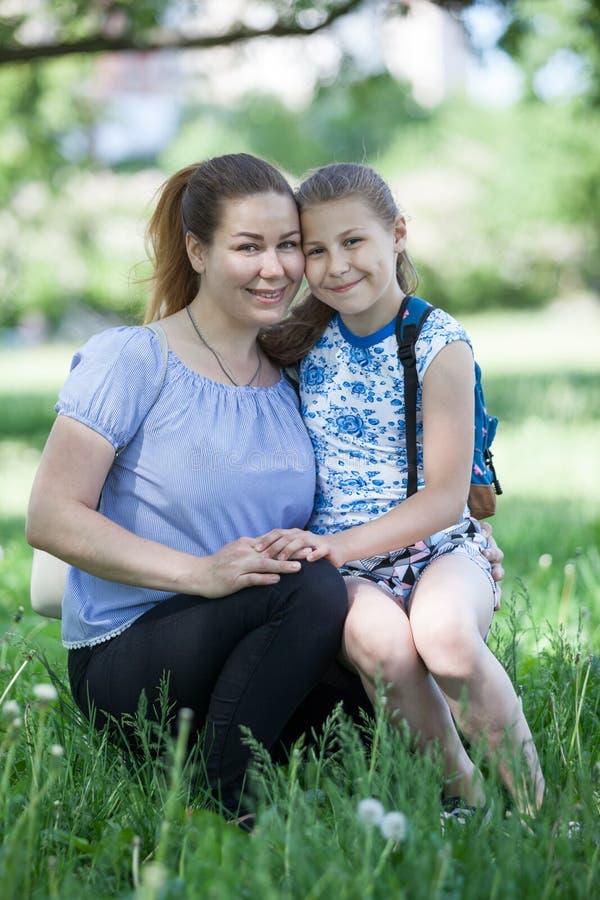 Retrato da mãe e dos seus dez anos da filha idosa que senta-se na grama verde, abraçando, sorrindo e olhando a câmera fotos de stock royalty free