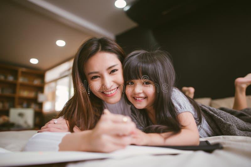 Retrato da mãe e da filha que jogam e que escrevem em casa no quarto imagens de stock