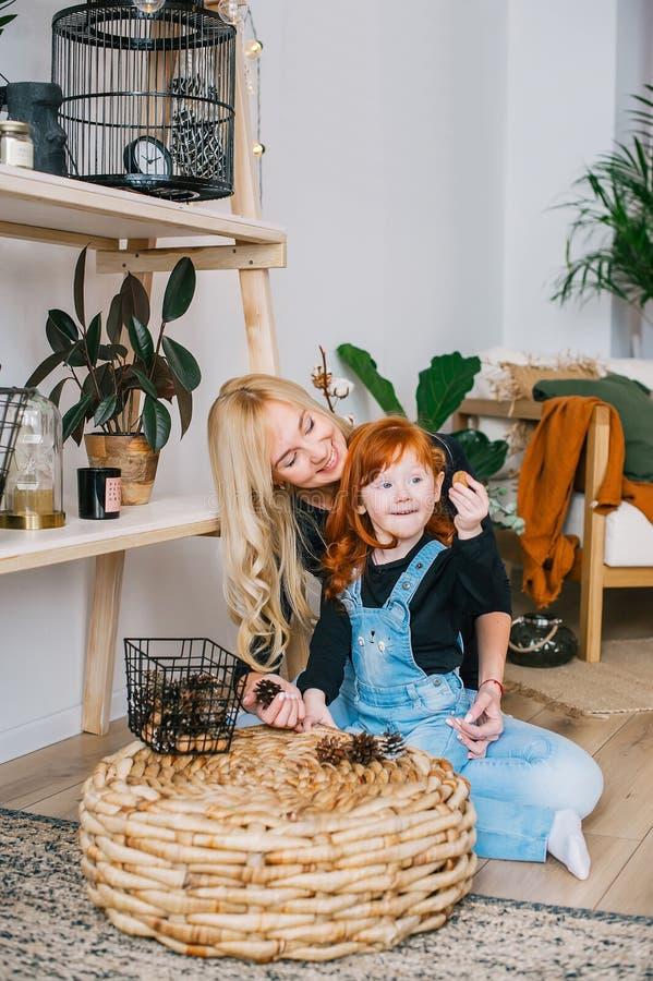 Retrato da mãe e da sua filha do ruivo na sala de casa Menina que sorri e que joga com cone do pinho fotos de stock royalty free