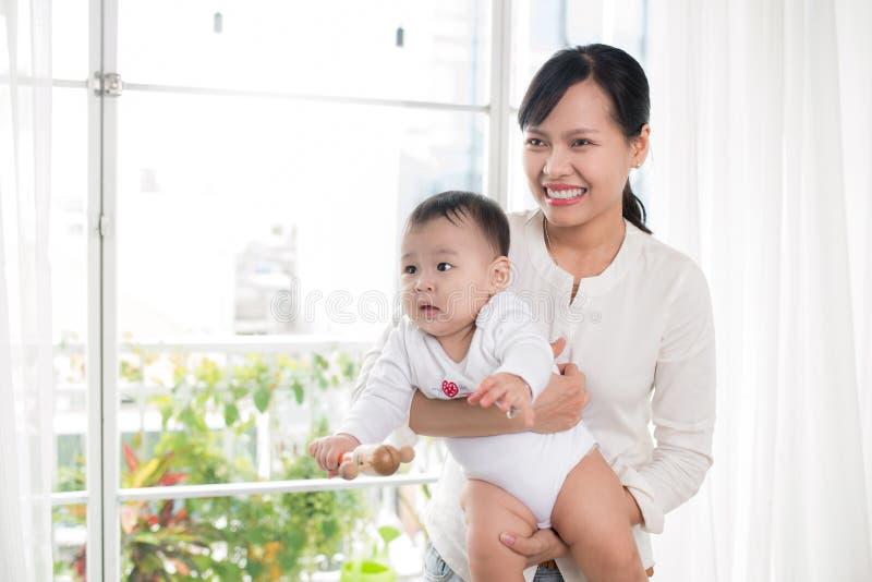 Retrato da mãe feliz e do bebê asiáticos que têm o divertimento junto em h fotos de stock