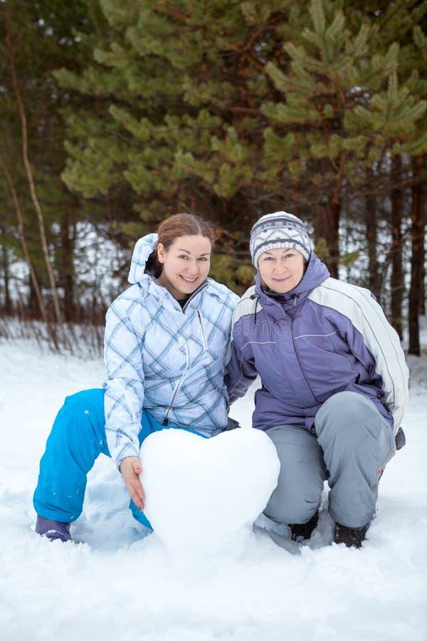 Retrato da mãe madura com sua filha adulta com a bola de neve na forma do coração, estação do inverno fotografia de stock