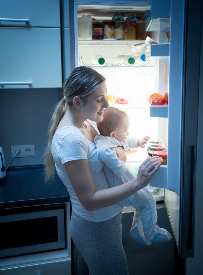 Retrato da mãe nova que procura o alimento no refrigerador na noite para alimentar seu bebê pequeno foto de stock royalty free